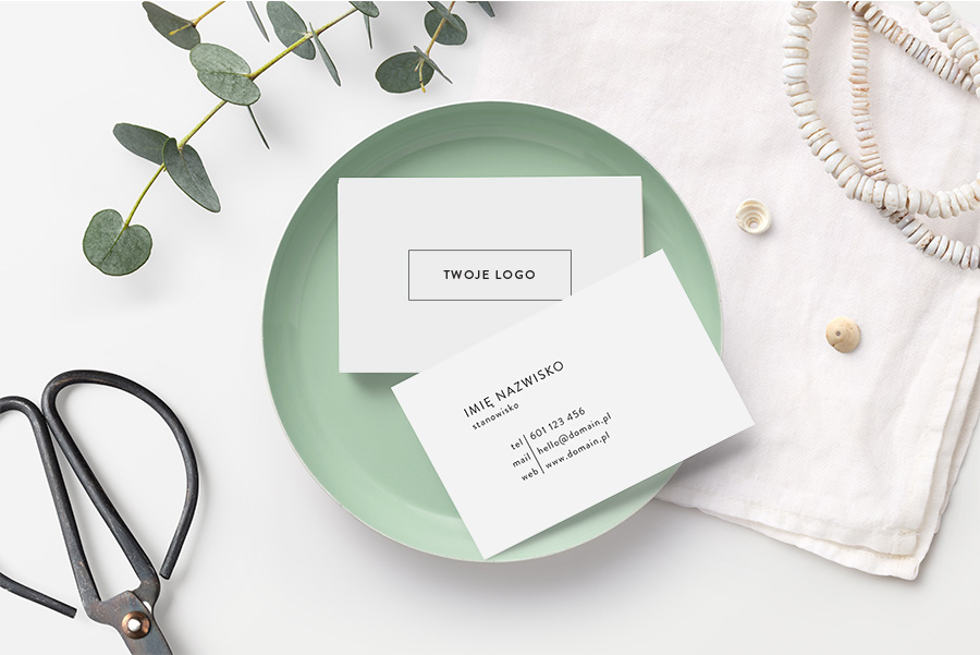 business card mockup with stack of cards in a small bowl, scissors, boho necklace and eucalyptus twigs on a styled desk. Mint, white and neutral hues. Flat lay